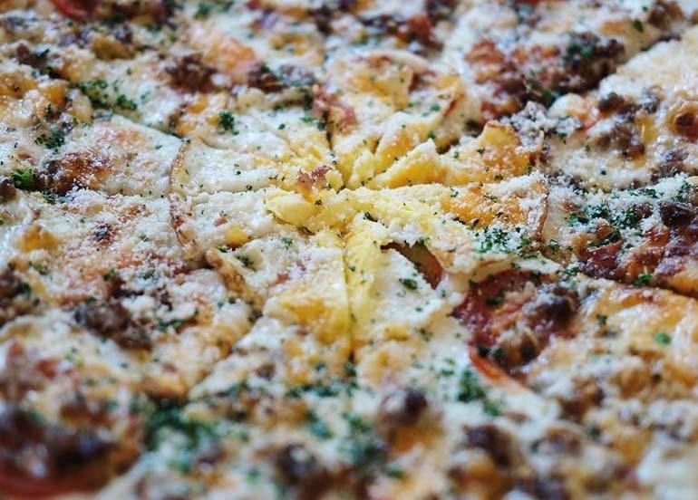 Vigan Pizza topped with cheese, vigan longganisa, and herbs