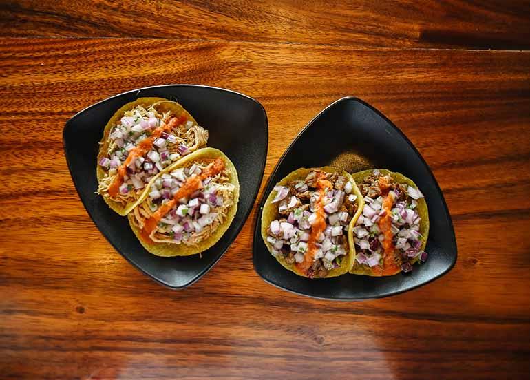Carne Asada Taco and Braised Carnitas Taco from Vatos Urban Tacos.