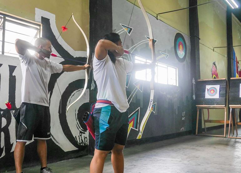 couple-aiming-bow-and-arrows