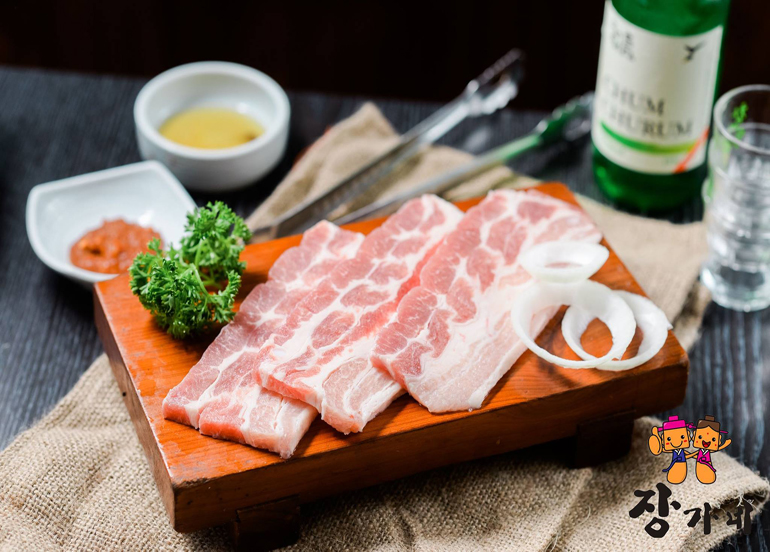 Three slices of samgyupsal laid on a board with Soju and dipping sauces in the background