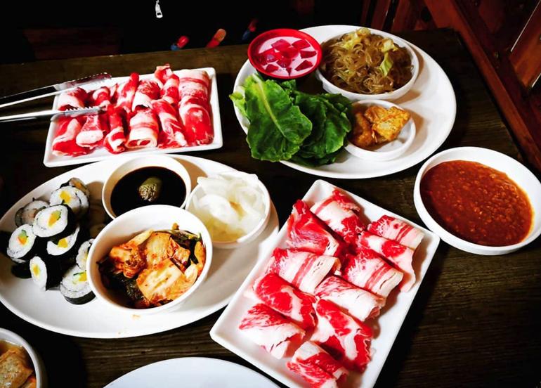 raw samgyupsal, kimbap, kimchi, japchae, and samjang