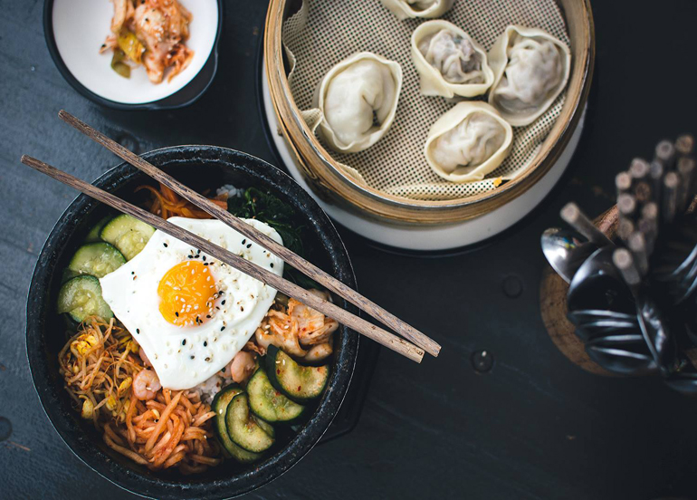 Bibimbap and Korean dumplings with chopsticks and utensils