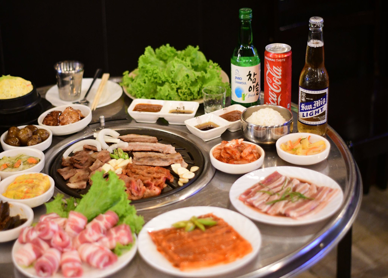 Assortments of meat cuts, side dishes, and beverages such as beer, soju, and coke