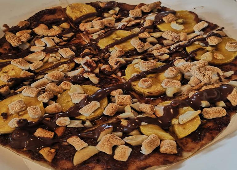 Hazelnut Banana Crunch Dessert Pizza drizzled with hazelnut sauce, bananas, marshmallows, and nuts