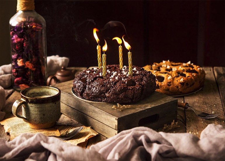 Quadruple Chocolate Celebration Cookie Cake topped with four candles