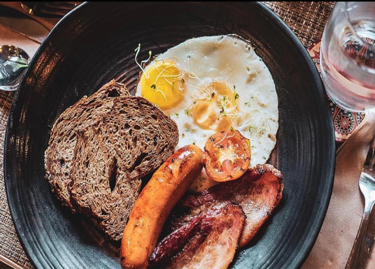 Burrow Cafe Breakfast with toast, eggs, banana, and slabs of bacon