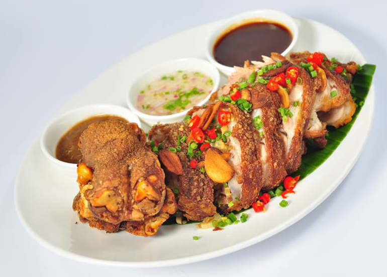 Boneless Crispy Pata topped with chili, chives, and garlic with sides of vinegar and liver sauce from Tipulo Filipino