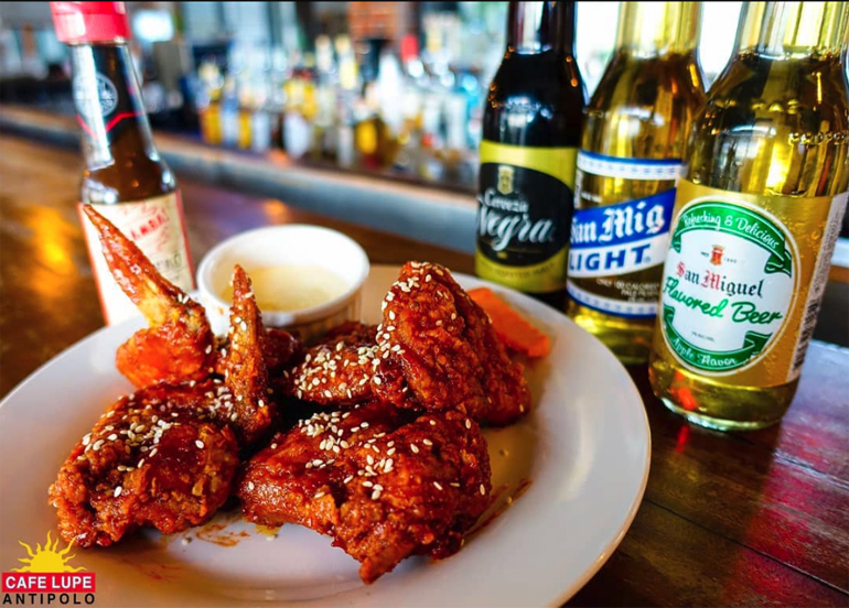 Buffalo wings topped with sesame seeds paired with an assortment of beers from Cafe Lupe