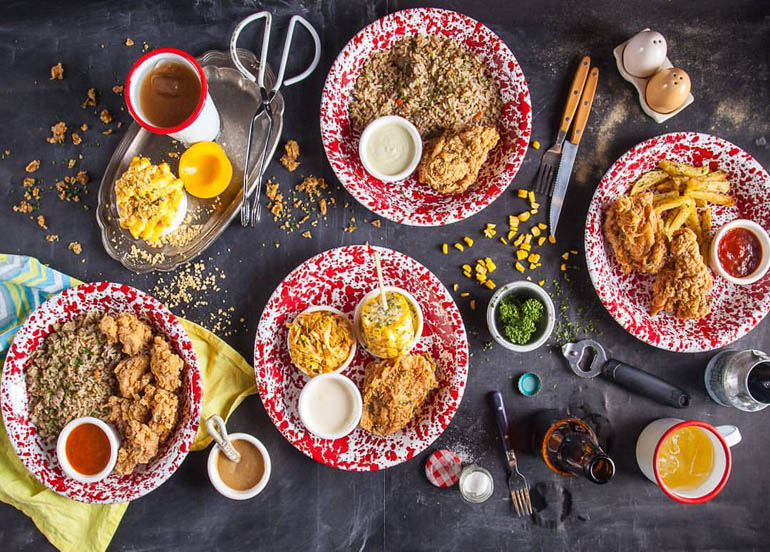 Flatlay of Birdhouse's fried chickenn meals, assortment of sauces, and sides